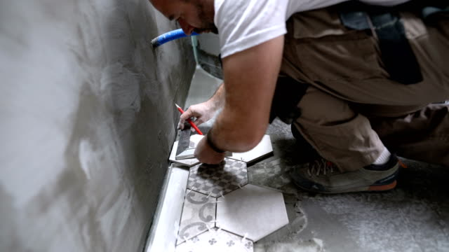 Tile professional measuring and preparing tile for installation