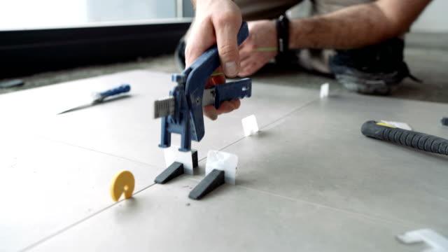 tiler fästseparatorer mellan nyinstallerade plattor - construction workwear floor bildbanksvideor och videomaterial från bakom kulisserna