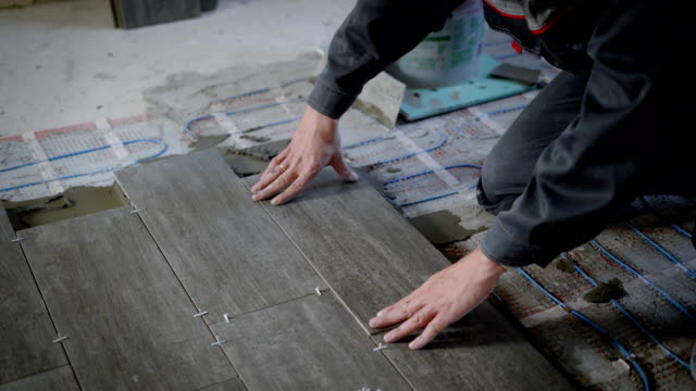 tiler is lying tile on a floor, pressing down and regulating, installing plastic industrial crosses for fixing - piastrella video stock e b–roll