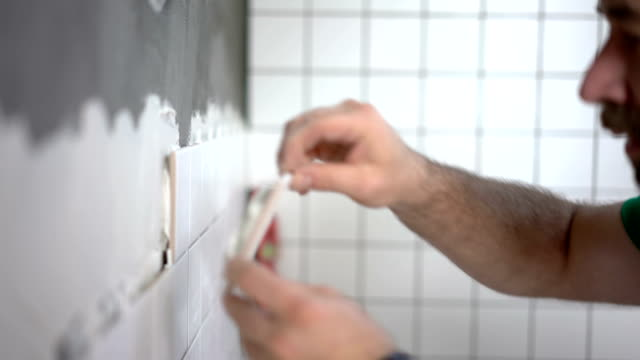 Tiler placing ceramic tile on the wall Close-up footage of tile mason installing ceramic tiles on the bathroom wall renovation stock videos & royalty-free footage