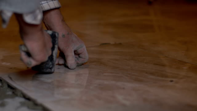 Tiler tiling the floor Close up shot of an unrecognizable tiler fixing a tile on a fresh tile adhesive on the floor. Also available in 4K resolution. craftsman architecture stock videos & royalty-free footage
