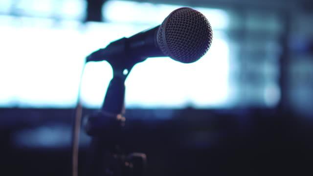 schräg nach unten nahaufnahme mikrofon in raum mit spotlight - aufnahmegerät stock-videos und b-roll-filmmaterial