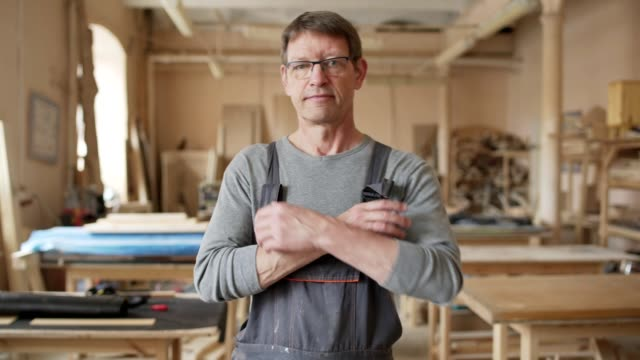 Tilt down of mature furniture maker in eyeglasses and work overalls walking towards camera in his workshop and standing cross-armed looking at camera