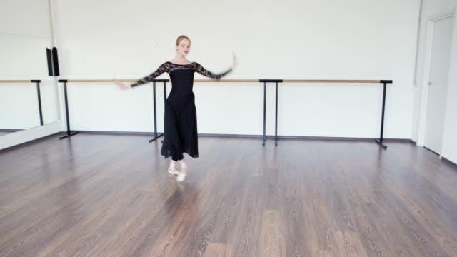 tilt-down schwenkschuss von professionellen ballerina in pointe-schuhe proben allein in tanzstudio mit barre und spiegel an den wänden - gymnastikanzug stock-videos und b-roll-filmmaterial