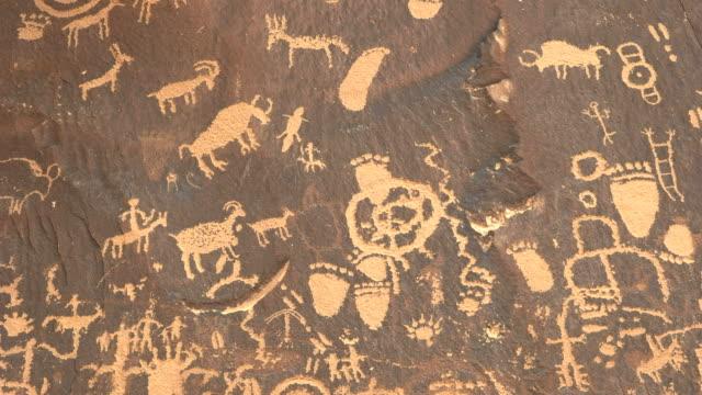 tilt down shot of ancient american indian drawings on newspaper rock in utah