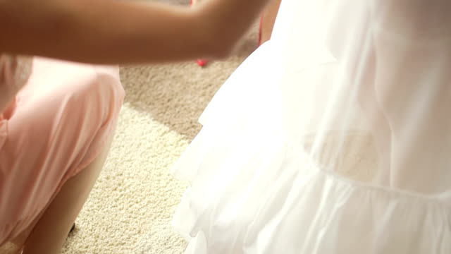 Tilt down shot of woman dressing up bride. Cropped image of female buttoning wedding dress. She is fastening pearl buttons of jacket. video