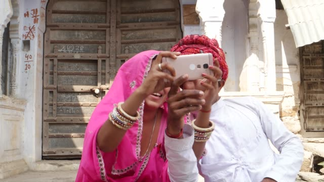 tilt down to a traditional couple taking camera selfie on mobile phone photography in rajasthan india - sari filmów i materiałów b-roll