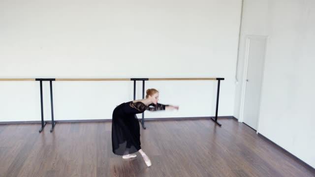 kippen sie weit schuss von eleganten jungen ballerina in pointe schuhe, schwarzes trikot und lange wickeln rock tanz in der probe im tanzstudio - gymnastikanzug stock-videos und b-roll-filmmaterial