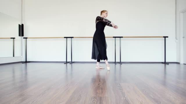 kippen sie einen weiten schuss von anmutigen ballerina in pointe-schuhe, schwarze spitze trikot und lange wickeln rock proben allein in tanzstudio mit spiegeln und barre an den wänden - gymnastikanzug stock-videos und b-roll-filmmaterial
