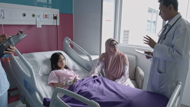 Tilt film video of doctor speaking to mother and child patient in hospital bed