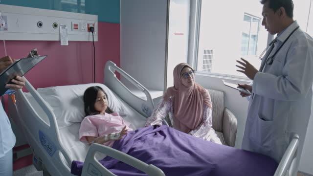 tilt-film-video der arzt im gespräch mit mutter und kind patient im krankenhausbett - krankenstation stock-videos und b-roll-filmmaterial