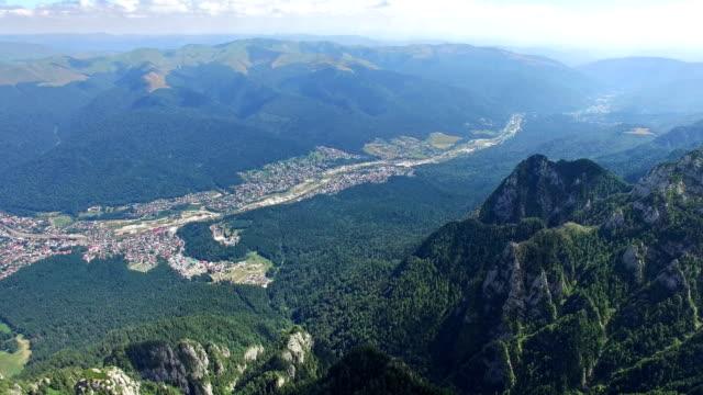 Tilt from Caraiman Peak to Bucegi city, aerial flight, Romania video