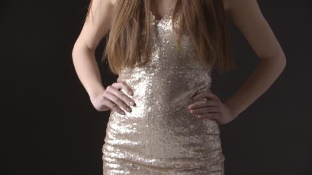 inclinazione colpo di elegante giovane donna in abito da sera scintillante - mani sui fianchi video stock e b–roll