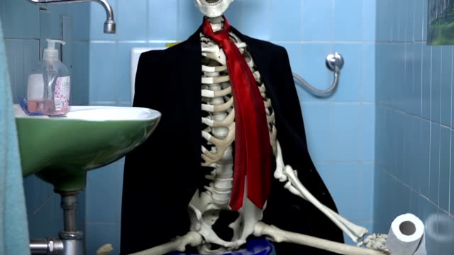 Tilt shot of skeleton in business clothes sitting on toilet Skeleton is sitting on the toilet to take care of his biological needs animal skeleton stock videos & royalty-free footage