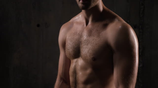 Tilt up and down of strong man in sport shorts with bare torso posing in studio video