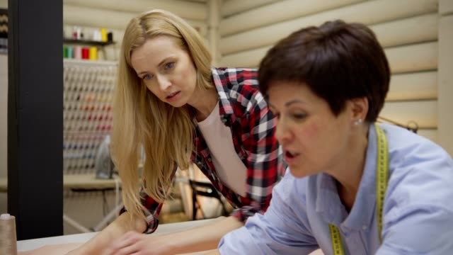 Tilt up and down side view of cheerful middle aged female tailor explaining to young student how to draw paper sewing patterns standing at table in workshop Tilt up and down side view of cheerful middle aged female tailor explaining to young student how to draw paper sewing patterns standing at table in workshop young singles stock videos & royalty-free footage