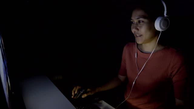 4 k ms は、アジアの女性が自宅の暗闇の中でコンピューター ゲームを傾けます。 - ゲーム ヘッドフォン点の映像素材/bロール
