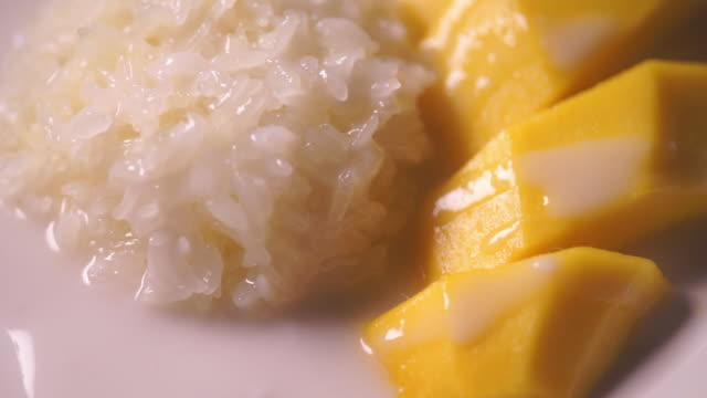 tilt up camera of sweet mango with sticky rice served on a white plate. - thai food stock videos and b-roll footage