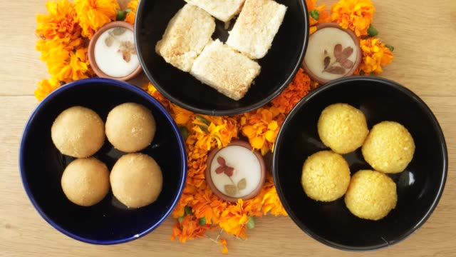 Tilt up close up across Indian sweets, flowers, diyas on a wooden background for Hindu festival of lights, Dusshera and Diwali preparation and celebration ingredients video
