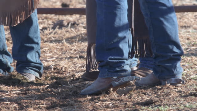 tilt up cowboy boots to ranchers discussing the days work - kowbojka praca związana z ziemią filmów i materiałów b-roll