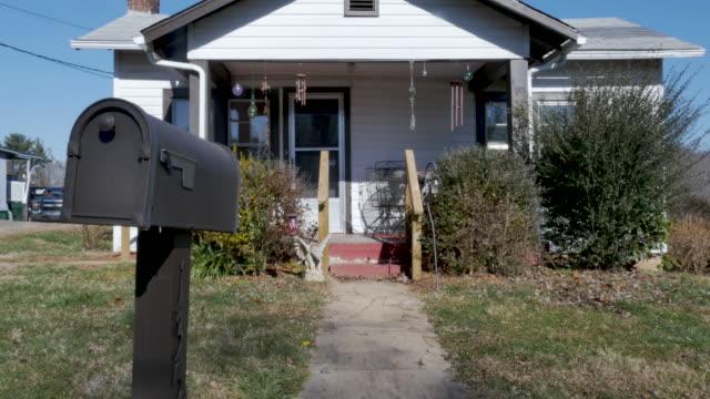 vídeos de stock e filmes b-roll de tilt up establishing shot of the entrance and walkway of a small one story house - house