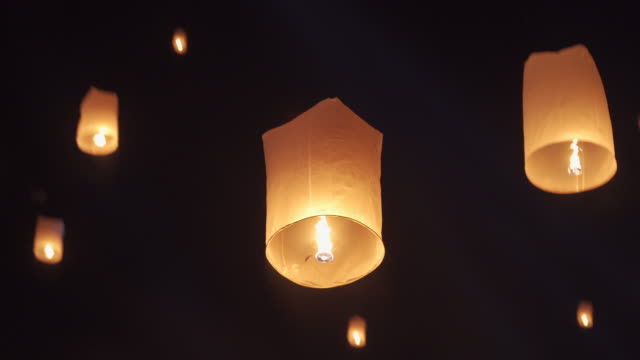 slo mo tilt up hand releasing lantern to the sky in yee peng festival (yi peng) - китайский фонарь стоковые видео и кадры b-roll