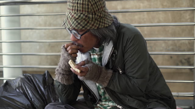Tilt up: Homeless eating food and sitting on footpath. Tilt up: Homeless senior men eating food and sitting on footpath in the morning. Text on the cardboard is a