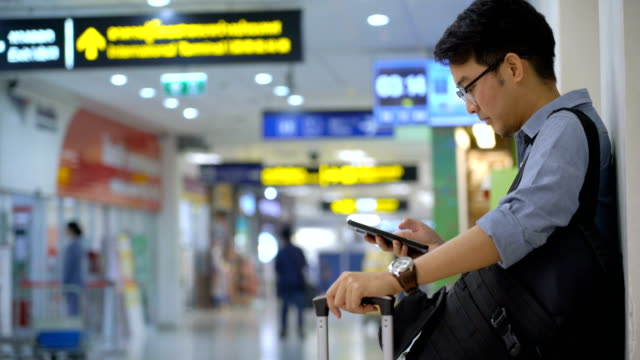 tilt up of asian man with baggage using mobile phone and walk away when the time is come - business travel stock videos and b-roll footage