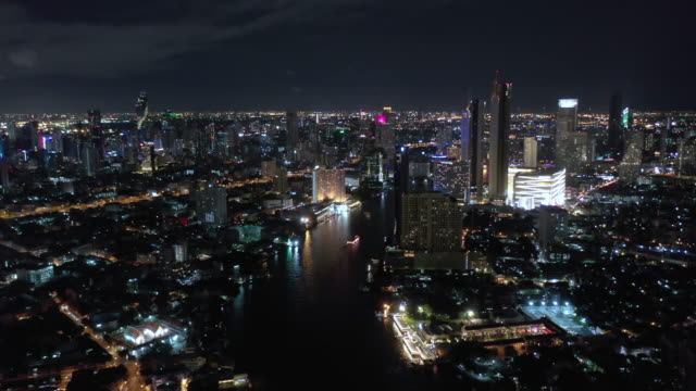 Tilt up of Chao Phraya River with Bangkok cityscape aerial view