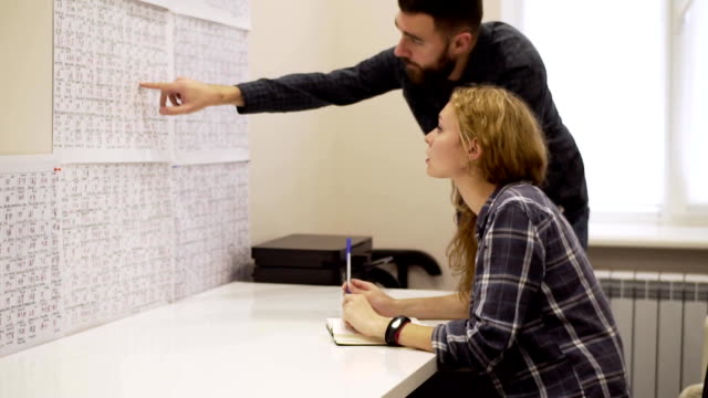 Tilt up of Guy and girl learn hieroglyphs in the office video
