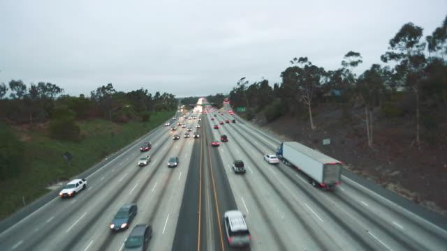 Tilt up of highway traffic shot from behind fence video