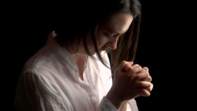 Tilt up on woman praying video