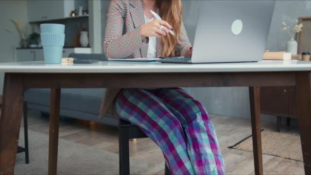 luta upp på unga blonda handledare kvinna i pyjamas byxor med hjälp av laptop video konferenssamtal för att leda klasser hemifrån på nätet. - byxor bildbanksvideor och videomaterial från bakom kulisserna