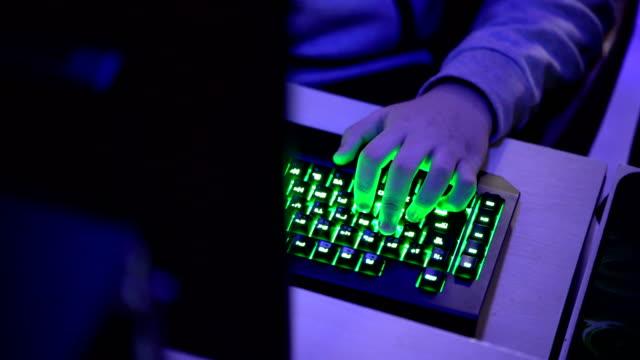 コンピューター ゲームのヘッドセットに直面するゲーマーの手からのショットを傾ける - pc 画面点の映像素材/bロール