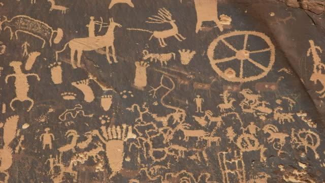 tilt up shot of american indian art on newspaper rock, utah