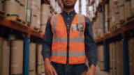 istock Tilt up shot of an african american young male warehouse operator portrait in safety hat standing in front of manufactured warehouse stock 1221315261