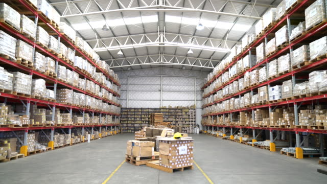 Tilt up shot of warehouse Tilt up shot of warehouse. Large quantity goods are arranged in shelves. Interior of illuminated workplace. warehouse stock videos & royalty-free footage
