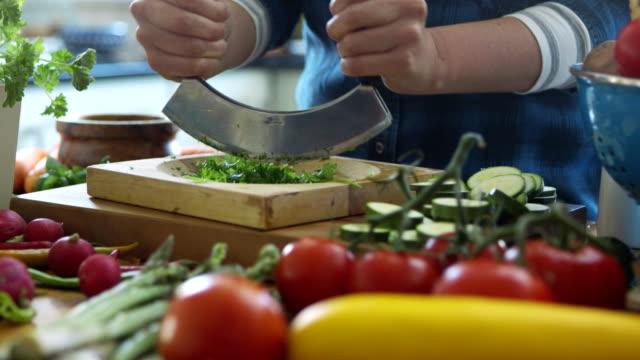 Tilt up shot of woman chopping cilantro using mincing knife video