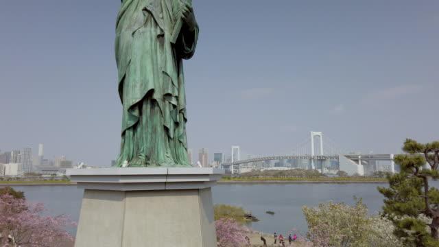 4k tilt upp frihets gudinnan i odaiba med rainbow bridge i tokyo, japan - odaiba kaihin koen bildbanksvideor och videomaterial från bakom kulisserna