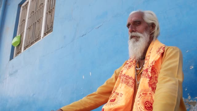 Tilt up to a Sadhu baba, Indian holy man, in between prayer looking straight at the camera Hindu male Sadhu or holy man elder in front of a blue background using communication technology in the holy city of Pushkar, Rajasthan indian culture stock videos & royalty-free footage