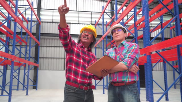 Tilt view of Two Asian man engineers point out to building structure in Warehouse