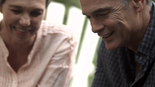 CU TILT_MS_Senior couple scrolling on smartphone together in garden video