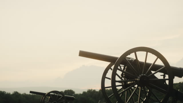 Tilting Down Shot of a Several US Civil War Cannons from Gettysburg National Military Park, Pennsylvania on a Hazy Day at Sunset