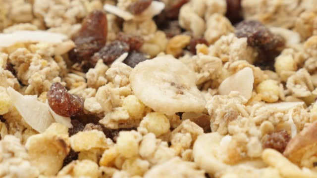 vídeos de stock e filmes b-roll de tilting on crunchy muesli pile in the bowl close-up 4k 2160p 30fps uhd video - cereals and corn flakes with dried fruits on table 4k 3840x2160 ultrahd footage - granola