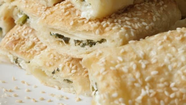vídeos de stock, filmes e b-roll de inclinando em folhas de massa rolos assados com queijo e recheio de espinafre 4k - comida salgada