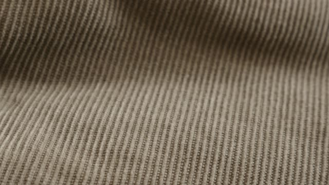 Tilting on fine cotton corduroy twisted fibers 4K 2160p 30fps UltraHD footage - Shallow DOF brown tufted parallel cords of velvet fabric slow tilt 3840X2160 UHD video
