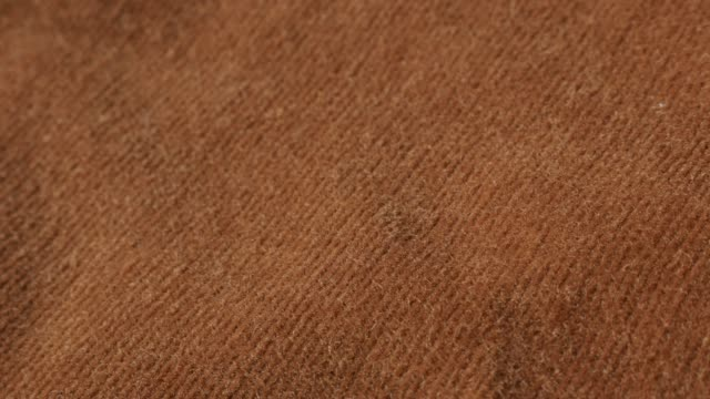 Tilting over corduroy striped brown pants fabric