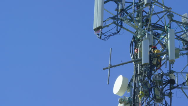 Tilting Up Shot of a Technician Assembling a Cell Phone Tower on a Clear, Sunny Day