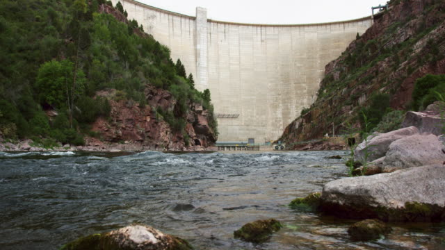 tilting up shot of the green river trickling over stones with flaming gorge dam in utah in the background - staudamm stock-videos und b-roll-filmmaterial