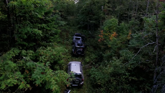 傾斜向上空中射擊的三個 suv 汽車停車在茂密的山林中。 - 亞洲中部 個影片檔及 b 捲影像